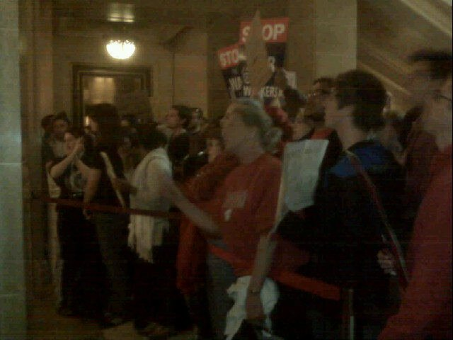 "Protesters lined up outside Gov. Walker's office chant, ""we're still here."""