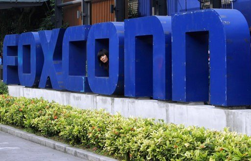 (AP Photo/Kin Cheung, File). FILE - In this May 27, 2010 file photo, a worker looks out through the logo at the entrance of the Foxconn complex in the southern Chinese city of Shenzhen. Conservationists are lining up to oppose Republican plans to elimi...