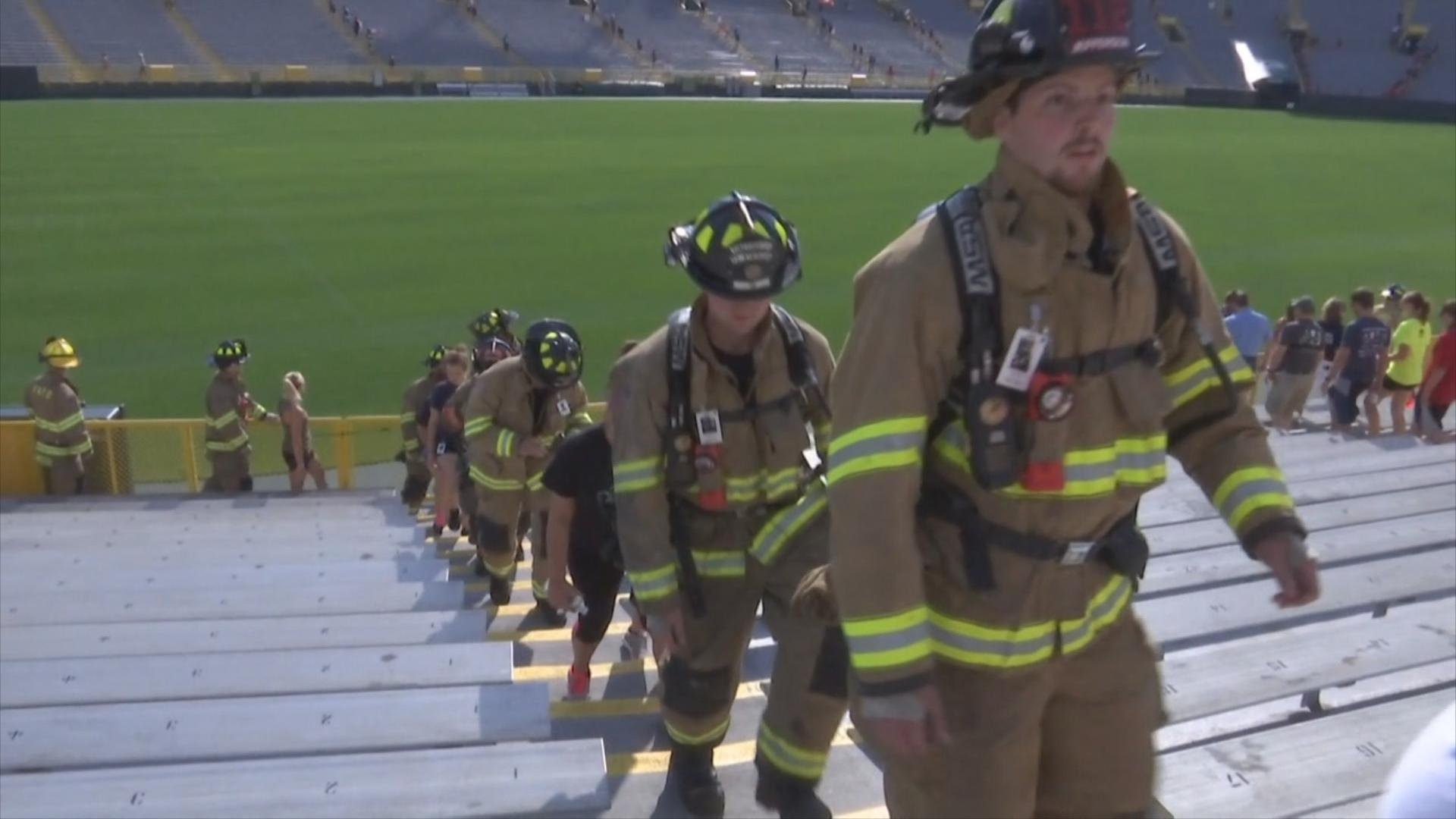 Firefighters climb the stairs at Lambeau Field to honor 9/11 fallen firefighters