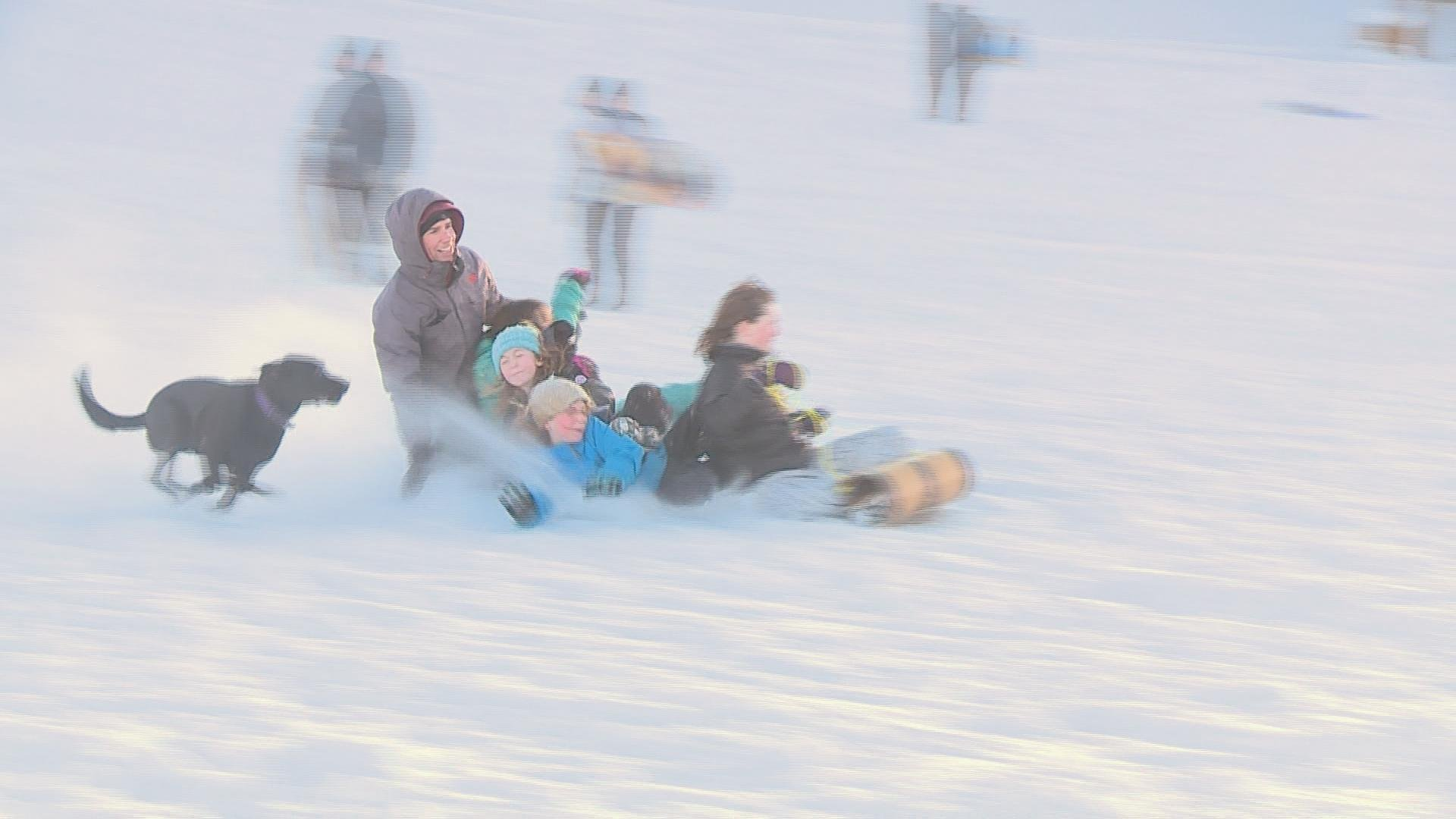 Jason Speich, his daughter Ivy, and her friends ride their sleigh down the hill at Elver Park during Snow Glow Friday.
