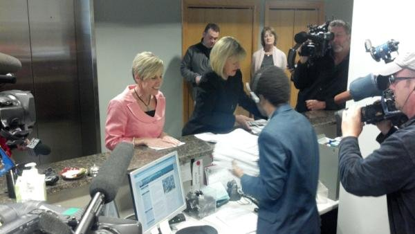 Kris Barrett turns in signatures on behalf of husband