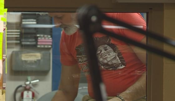 A volunteer works to repair the glass that was broken by a bullet.