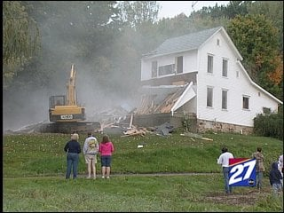 Sue Klang, left, looks on as a bulldozer tears down her home.  Volunteers from the Cazenovia community plan to rebuild the widow a home on the same spot.